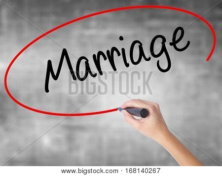 Woman Hand Writing Marriage With Black Marker Over Transparent Board