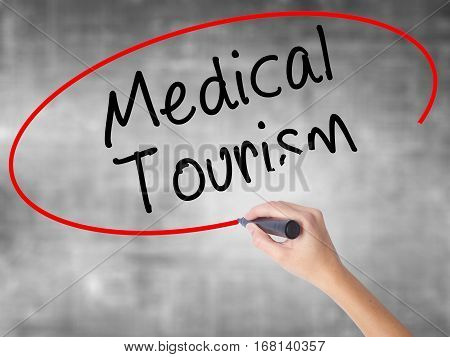 Woman Hand Writing Medical Tourism With Black Marker Over Transparent Board