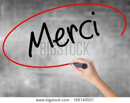 Woman Hand Writing Merci  (thank You In French) With Black Marker Over Transparent Board.