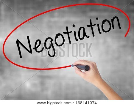 Woman Hand Writing Negotiation  With Black Marker Over Transparent Board.