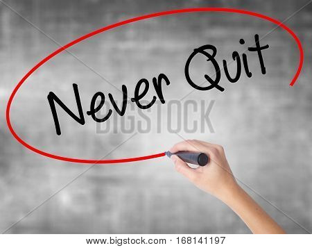 Woman Hand Writing Never Quit With Black Marker Over Transparent Board.