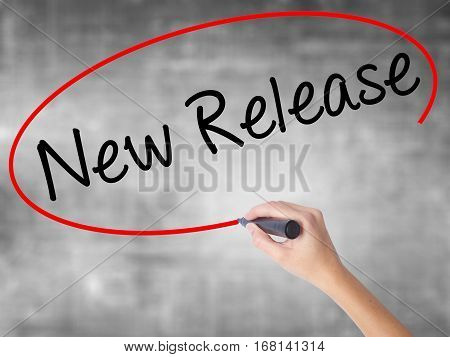 Woman Hand Writing New Release With Black Marker Over Transparent Board