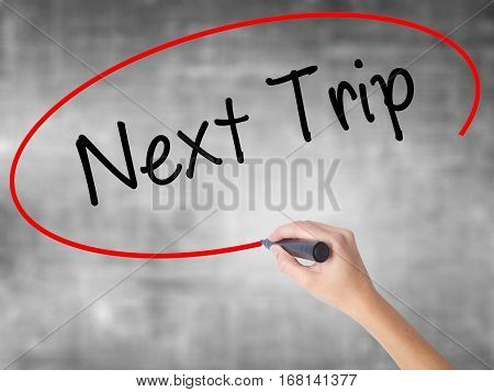Woman Hand Writing Next Trip With Black Marker Over Transparent Board