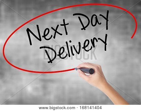 Woman Hand Writing Next Day Delivery With Black Marker Over Transparent Board.