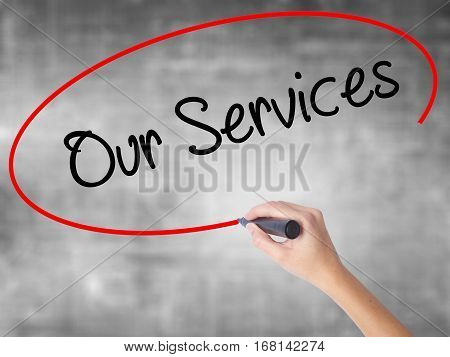 Woman Hand Writing Our Services With Black Marker Over Transparent Board