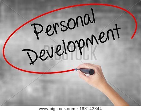 Woman Hand Writing Personal Development  With Black Marker Over Transparent Board.