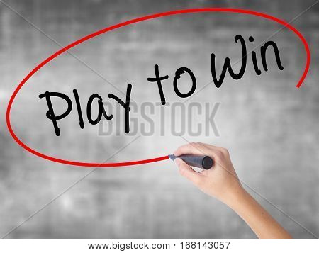 Woman Hand Writing Play To Win With Black Marker Over Transparent Board