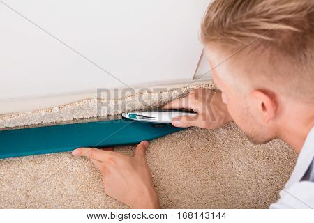 Close-up Of A Young Handyman Cutting Installing Carpet With Cutter poster