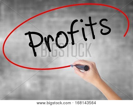Woman Hand Writing Profits With Black Marker Over Transparent Board.