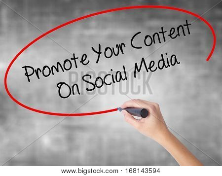 Woman Hand Writing Promote Your Content On Social Media  With Black Marker Over Transparent Board