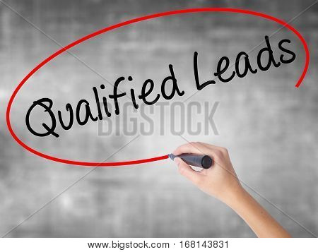 Woman Hand Writing Qualified Leads With Black Marker Over Transparent Board