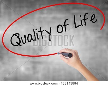 Woman Hand Writing Quality Of Life With Black Marker Over Transparent Board