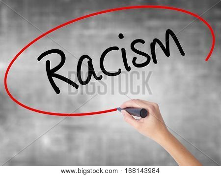 Woman Hand Writing Racism With Black Marker Over Transparent Board.
