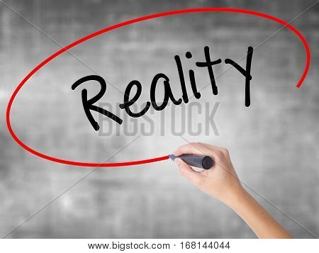 Woman Hand Writing  Reality With Black Marker Over Transparent Board