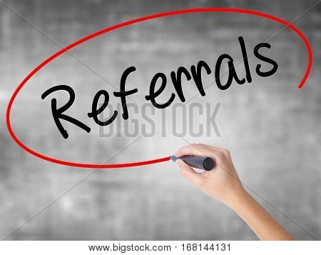 Woman Hand Writing Referrals With Black Marker Over Transparent Board.