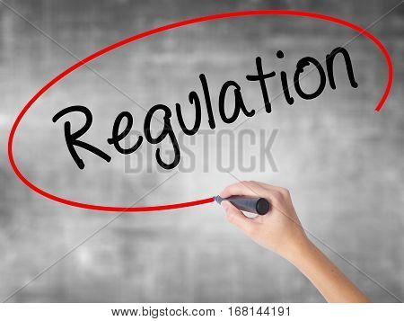 Woman Hand Writing Regulation  With Black Marker Over Transparent Board