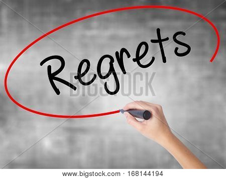 Woman Hand Writing  Regrets With Black Marker Over Transparent Board