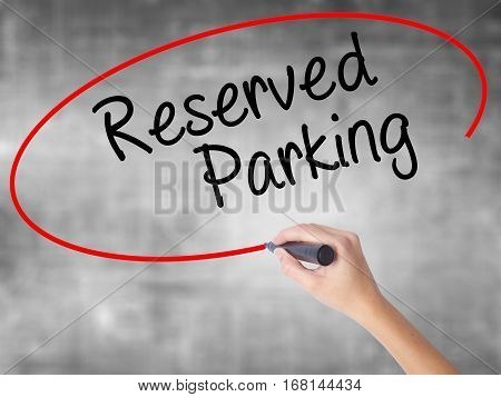 Woman Hand Writing Reserved Parking With Black Marker Over Transparent Board