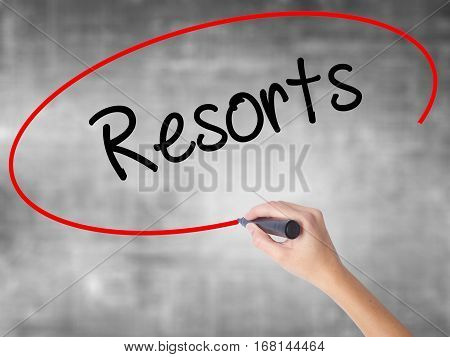 Woman Hand Writing Resorts  With Black Marker Over Transparent Board