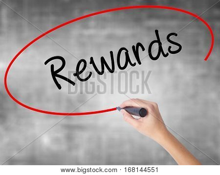 Woman Hand Writing Rewards With Black Marker Over Transparent Board