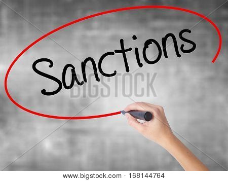 Woman Hand Writing Sanctions With Black Marker Over Transparent Board.