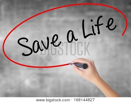 Woman Hand Writing Save A Life  With Black Marker Over Transparent Board