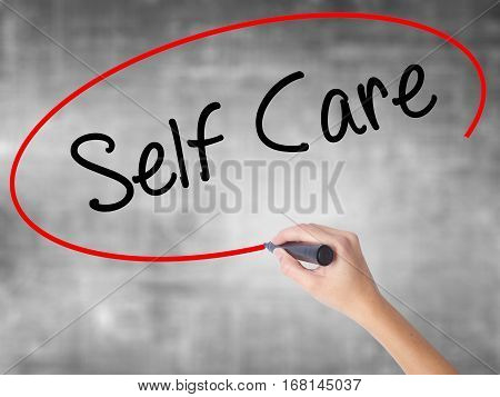Woman Hand Writing Self Care With Black Marker Over Transparent Board