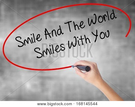 Woman Hand Writing Smile And The World Smiles To You With Black Marker Over Transparent Board