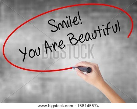 Woman Hand Writing Smile! You Are Beautiful With Black Marker Over Transparent Board