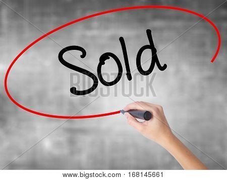 Woman Hand Writing Sold With Black Marker Over Transparent Board