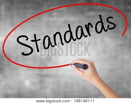 Woman Hand Writing Standards With Black Marker Over Transparent Board