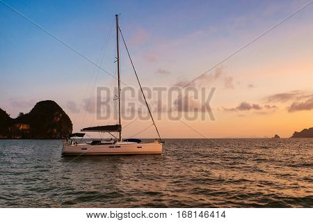 Yacht at sunset. Yacht on the islands background