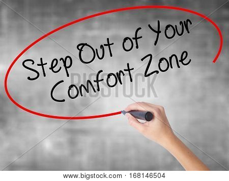 Woman Hand Writing  Step Out Of Your Comfort Zone With Black Marker Over Transparent Board.