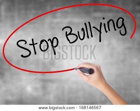 Woman Hand Writing Stop Bullying With Black Marker Over Transparent Board