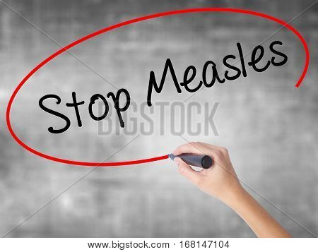 Woman Hand Writing Stop Measles  With Black Marker Over Transparent Board