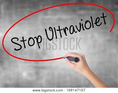 Woman Hand Writing Stop Ultraviolet With Black Marker Over Transparent Board