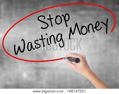Woman Hand Writing Stop Wasting Money With Black Marker Over Transparent Board