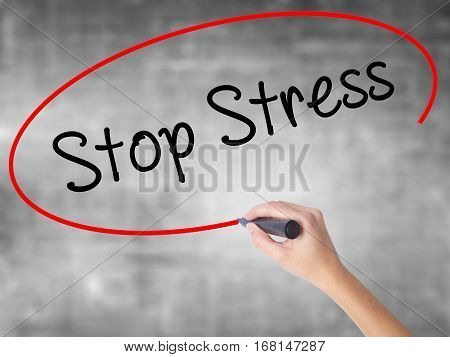 Woman Hand Writing Stop Stress With Black Marker Over Transparent Board