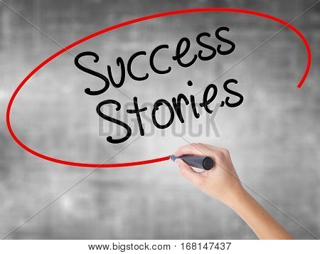Woman Hand Writing Success Stories With Black Marker Over Transparent Board
