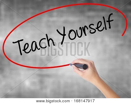Woman Hand Writing Teach Yourself  With Black Marker Over Transparent Board