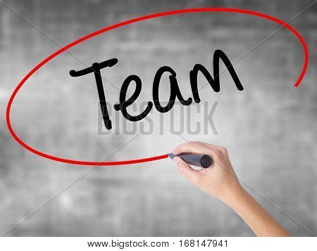 Woman Hand Writing Team With Black Marker Over Transparent Board