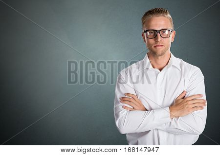 Portrait Of A Confident Young Businessman Against Grey Background