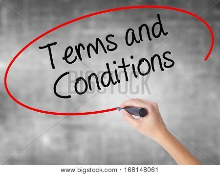 Woman Hand Writing Terms And Conditions With Black Marker Over Transparent Board