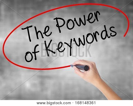 Woman Hand Writing The Power Of Keywords With Black Marker Over Transparent Board