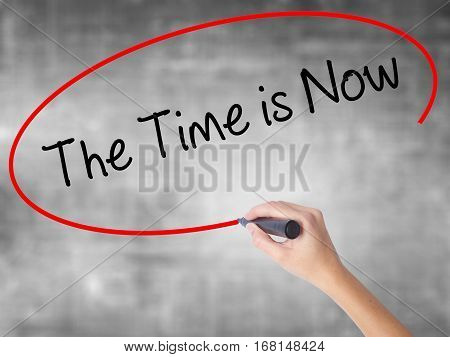 Woman Hand Writing The Time Is Now With Black Marker Over Transparent Board