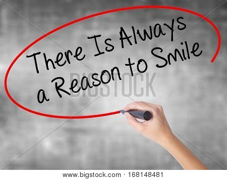 Woman Hand Writing There Is Always A Reason To Smile With Black Marker Over Transparent Board