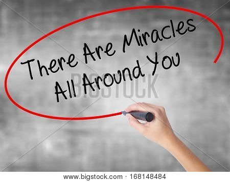 Woman Hand Writing There Are Miracles All Around You  With Black Marker Over Transparent Board