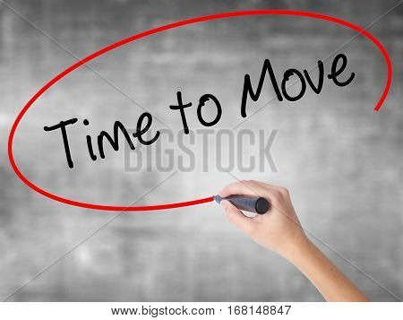 Woman Hand Writing Time To Move With Black Marker Over Transparent Board