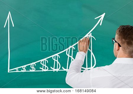 Businessman Showing Inflation Concept With Increasing Dollar Graph On Green Blackboard. Salary Growth Concept