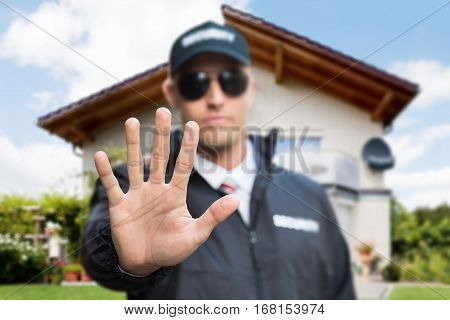 Close-up Of A Young Male Security Guard Making Stop Gesture In Front Of A House